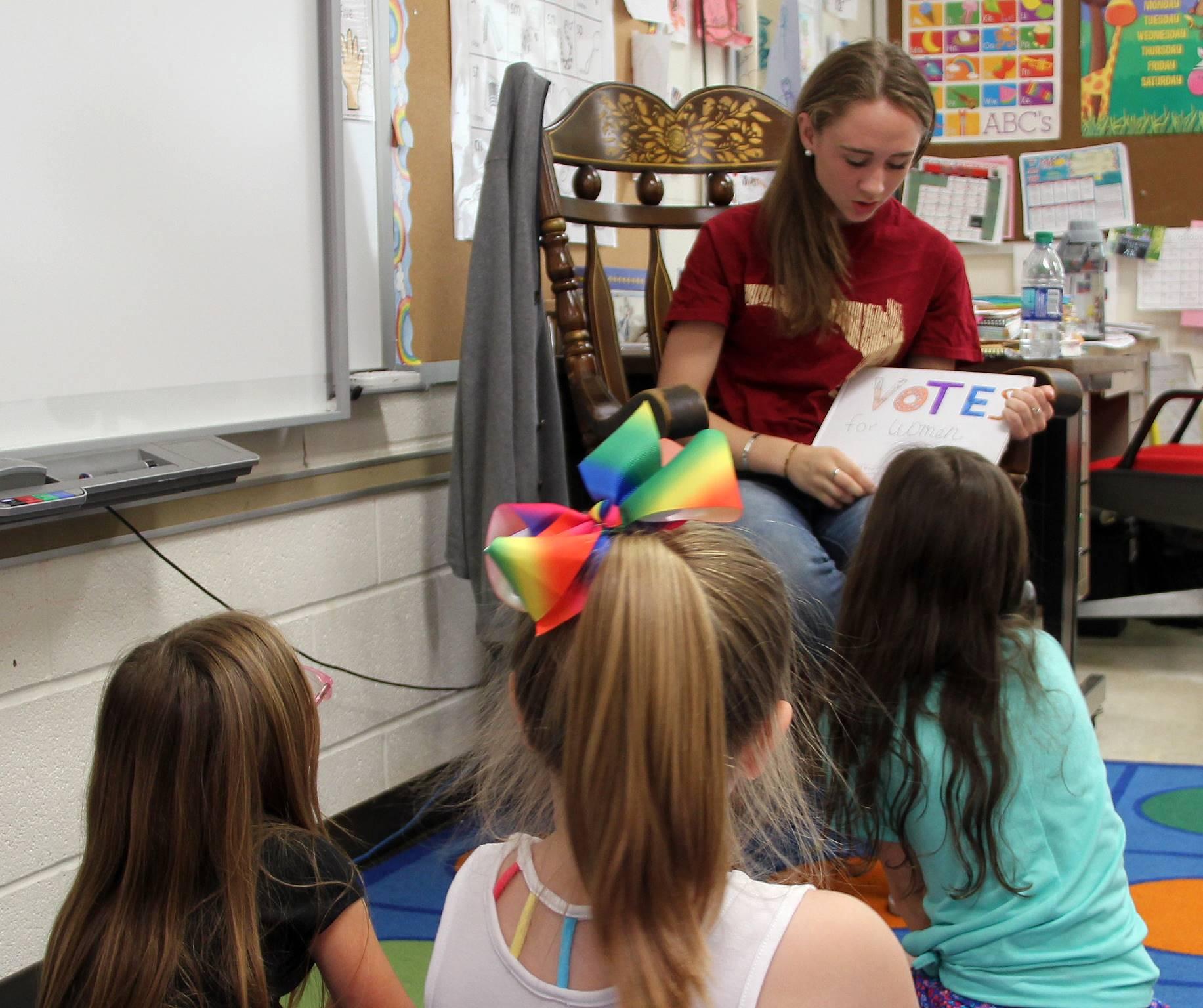 high school student reading to kindergarten students 2