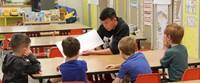 high school student reading to kindergarten students 1