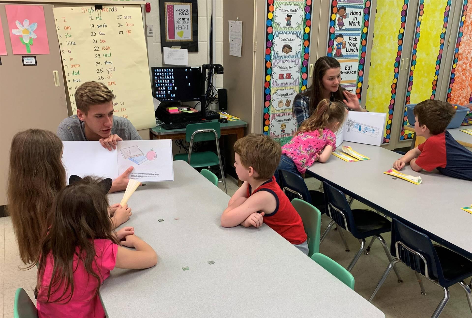 high school students reading to kindergarten students