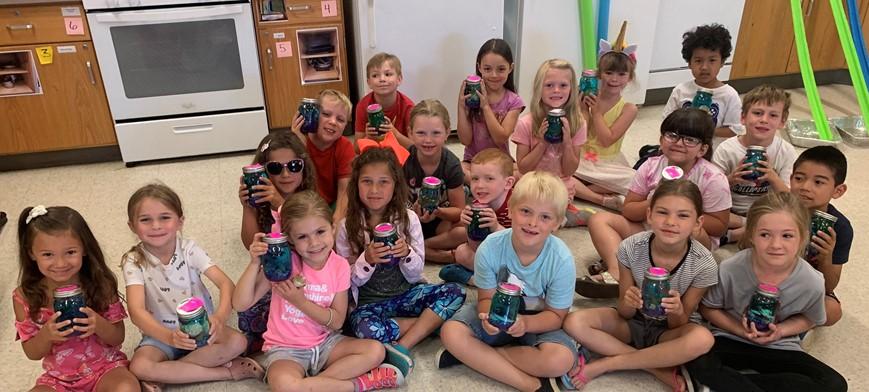 students holding aquarium jars