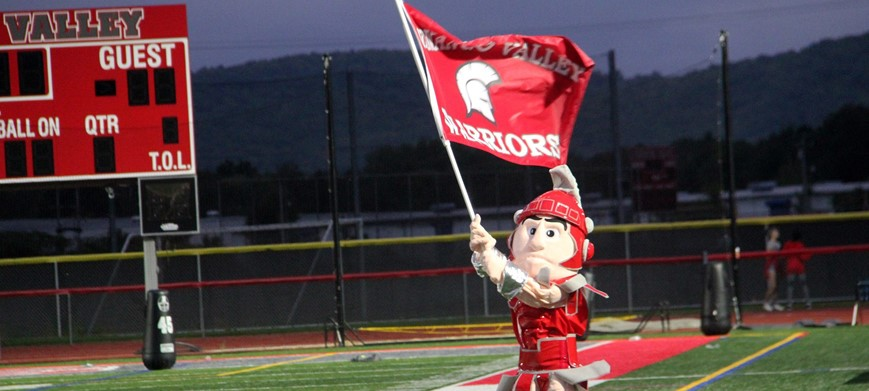warrior mascot running on field with flag