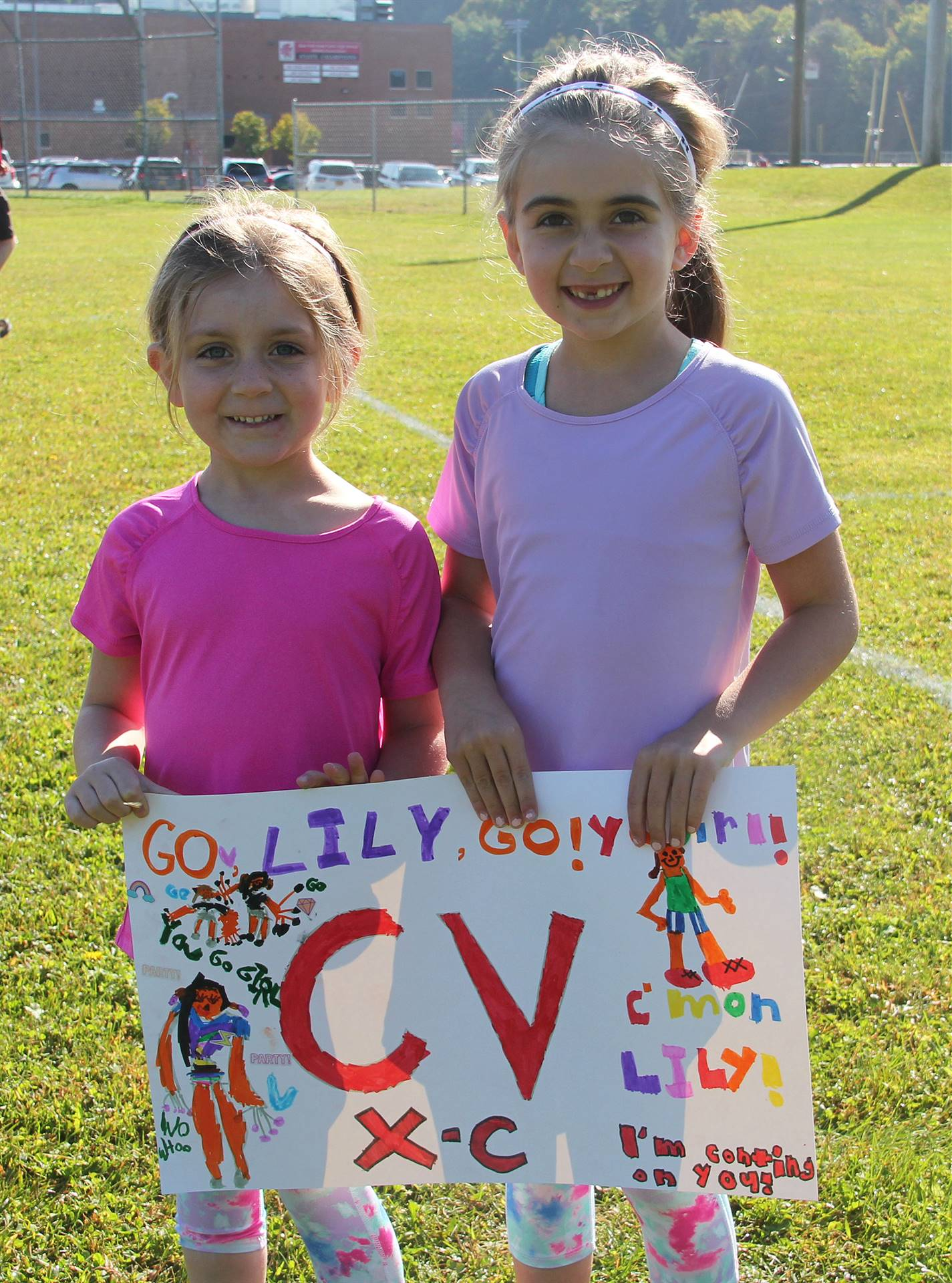 two students holding encouraging sign