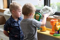 students playing in play kitchen