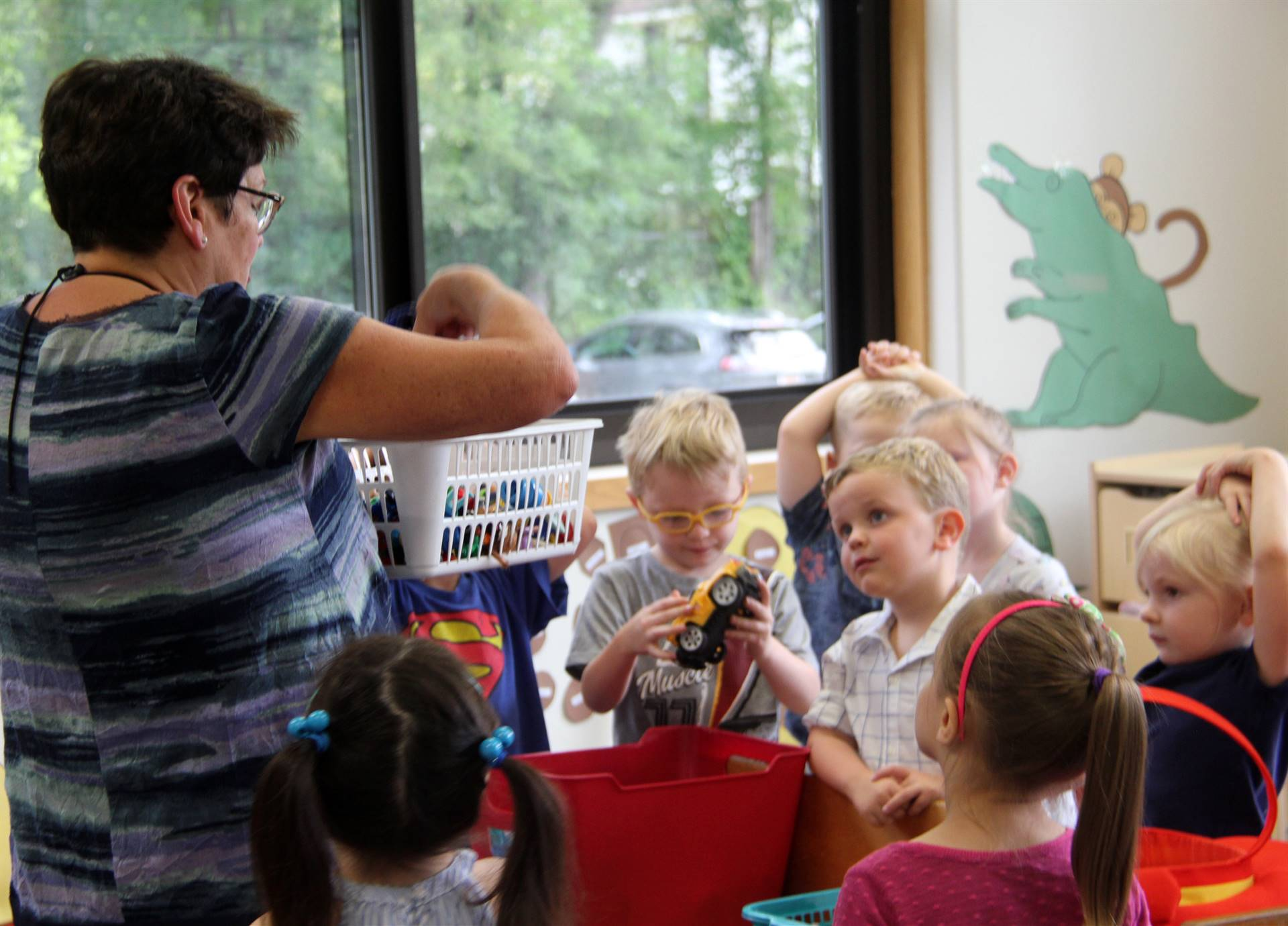 another photo of teacher showing students toys