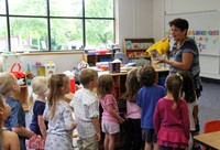 teacher showing students toys