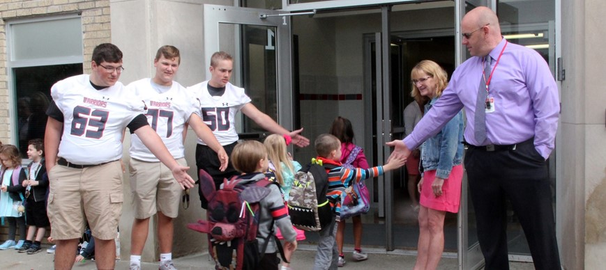 elementary students giving high school athletes high five as they enter school