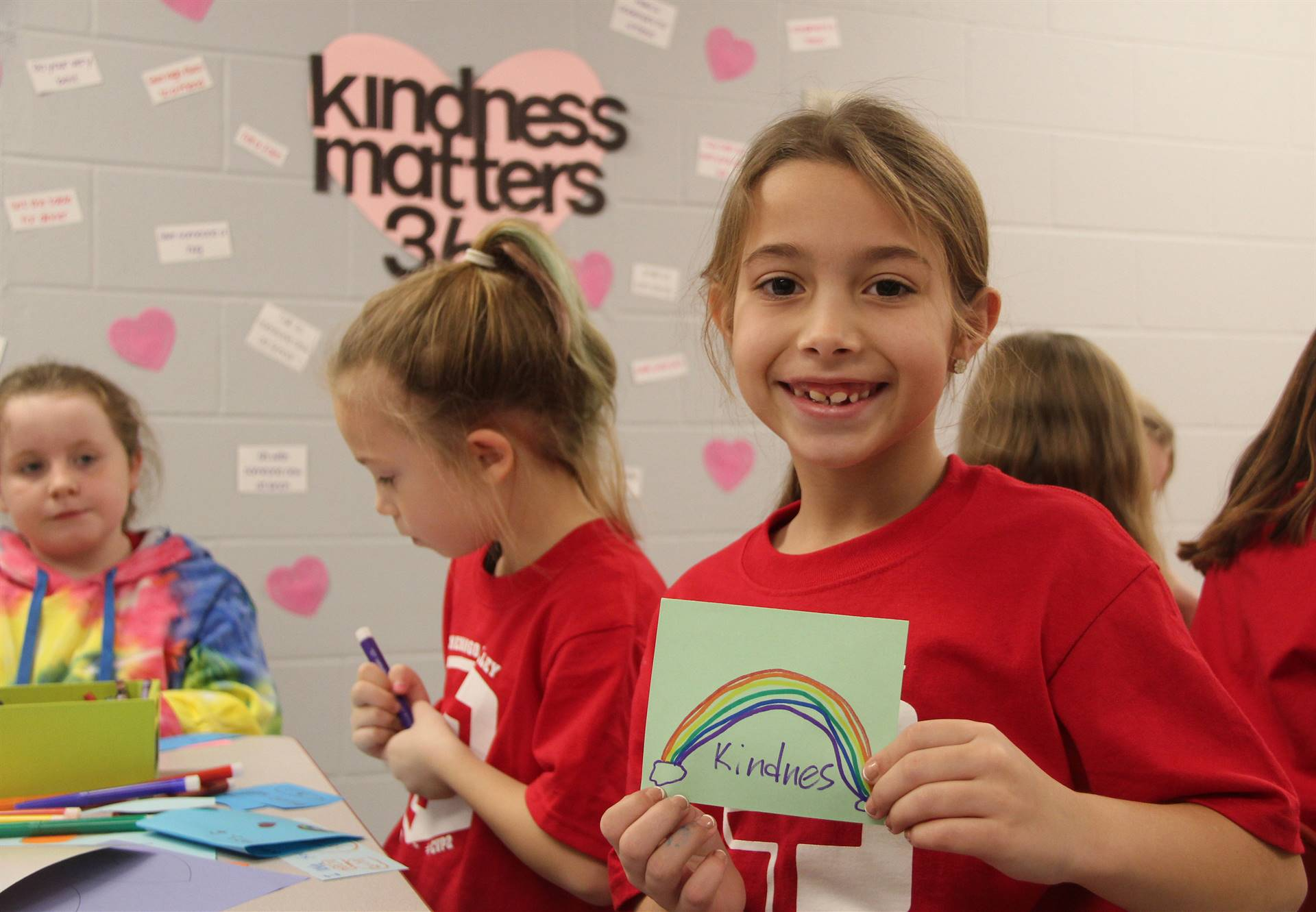student holding kindness card
