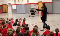 school counselor reading book to students at morning presentation