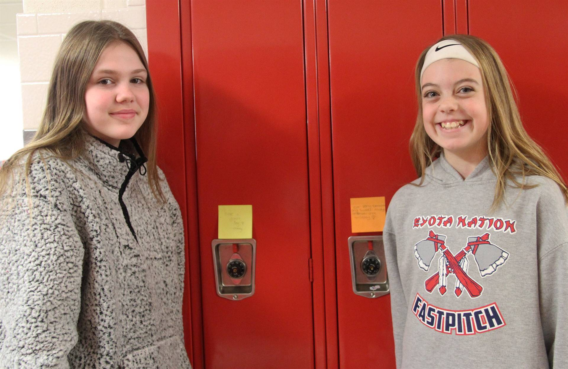 two students smiling next to lockers with positive post it notes