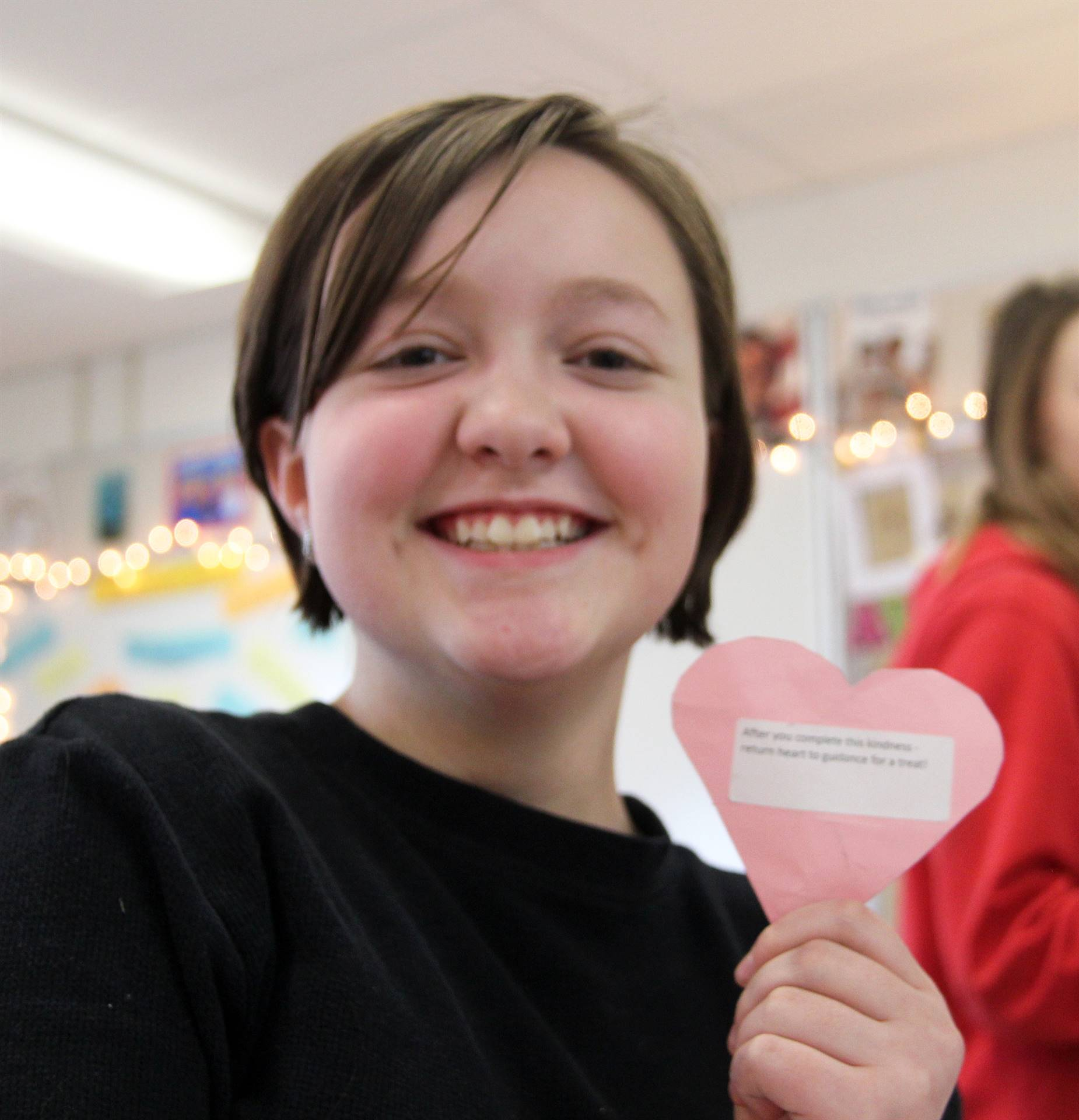 student smiling holding positive heart challenge