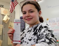 student smiling holding bookmark with random acts of kindness