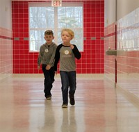 two students walking through hallway