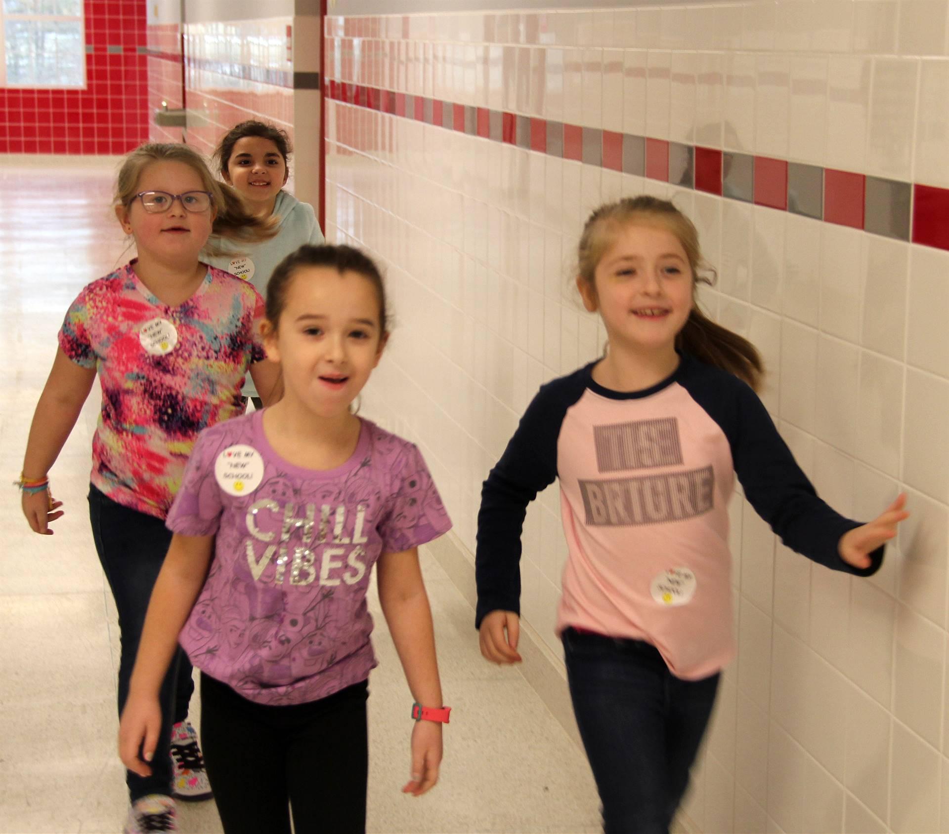 four students walking through hallway