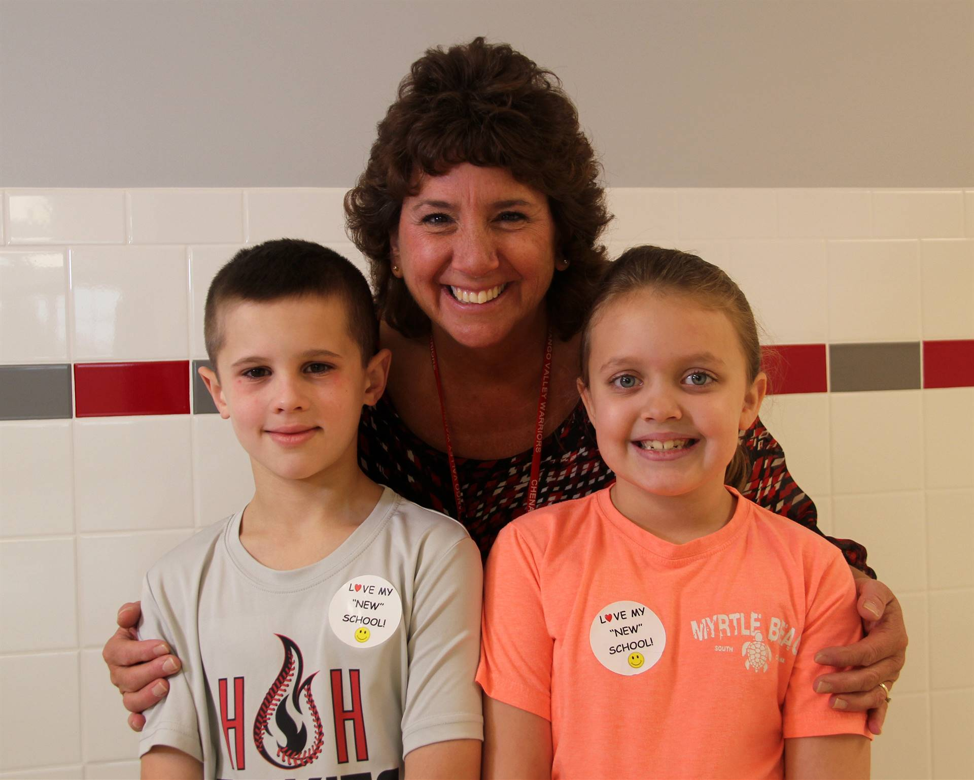 principal smiling with two students