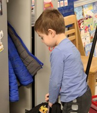 student putting backpack into cubby
