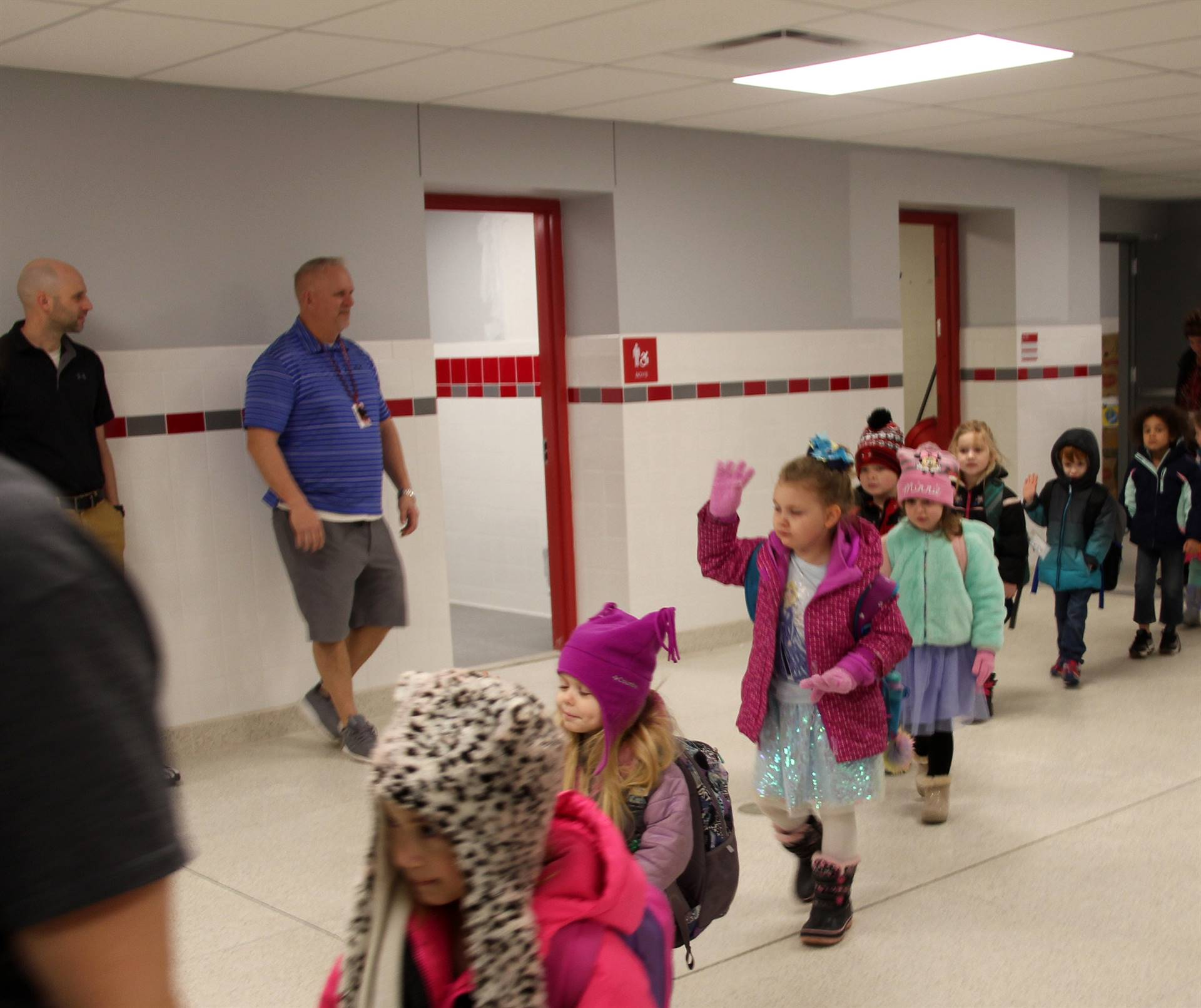 students waving in hallway