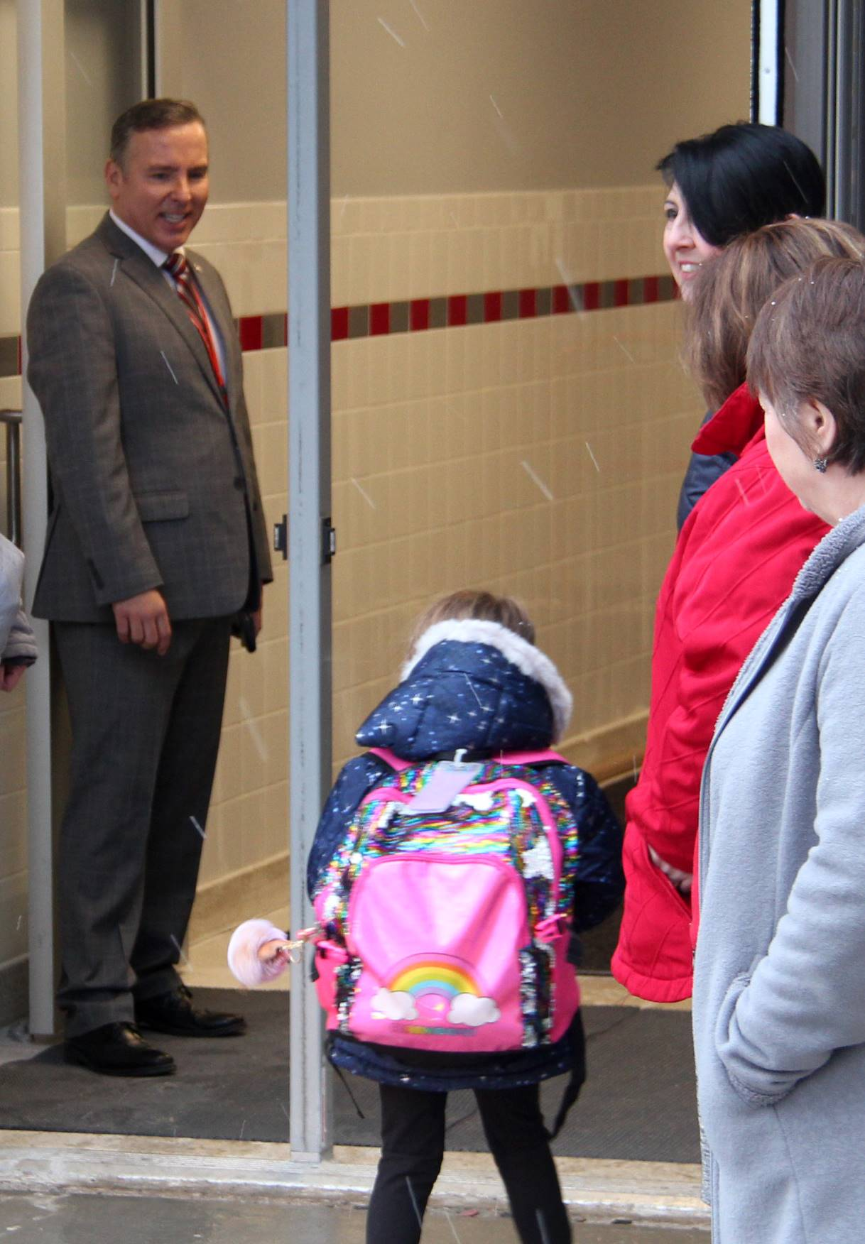 adults greeting students