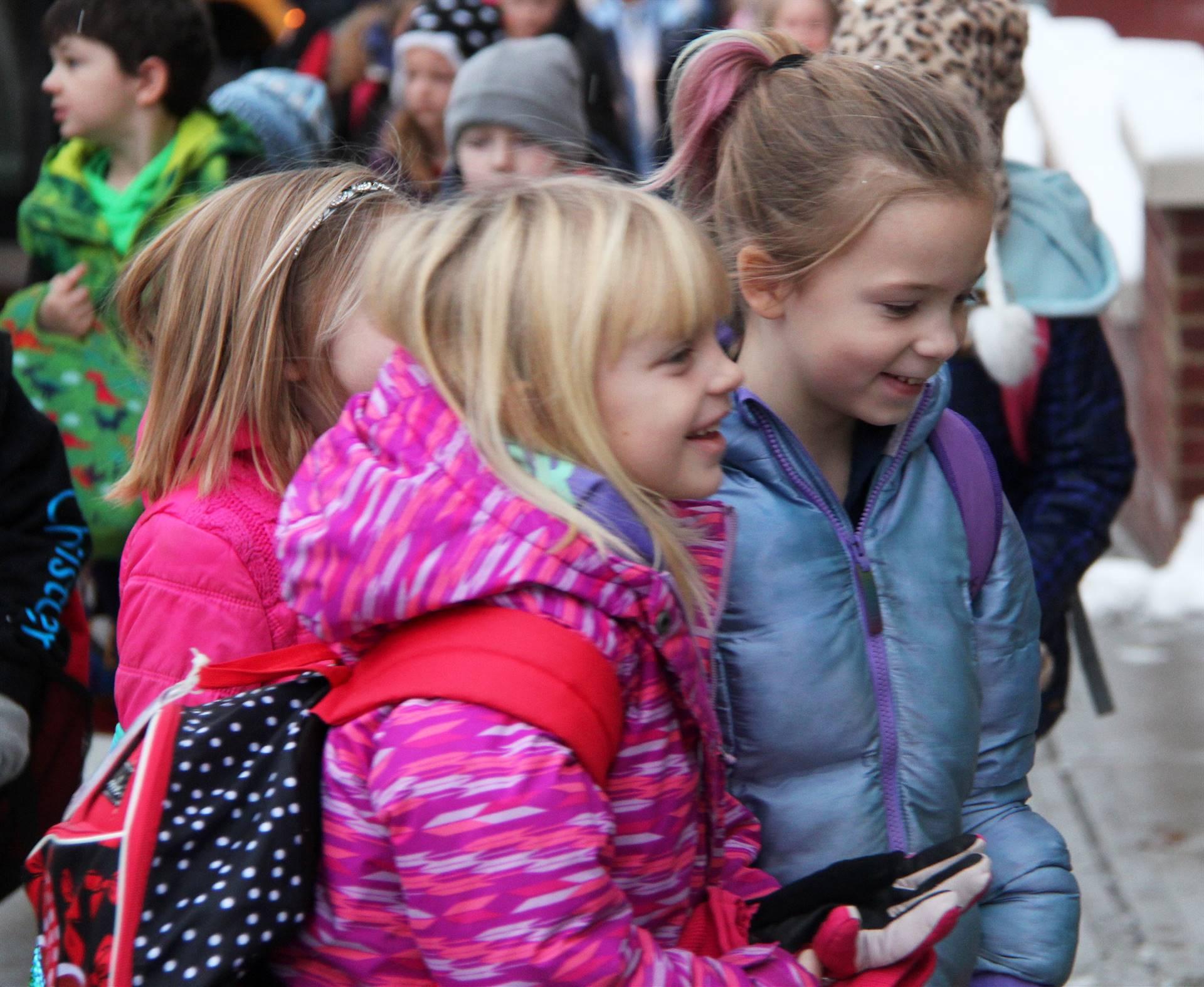 students smiling walking towards school