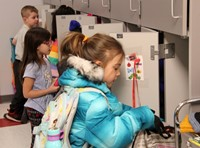 students putting items in cubbies