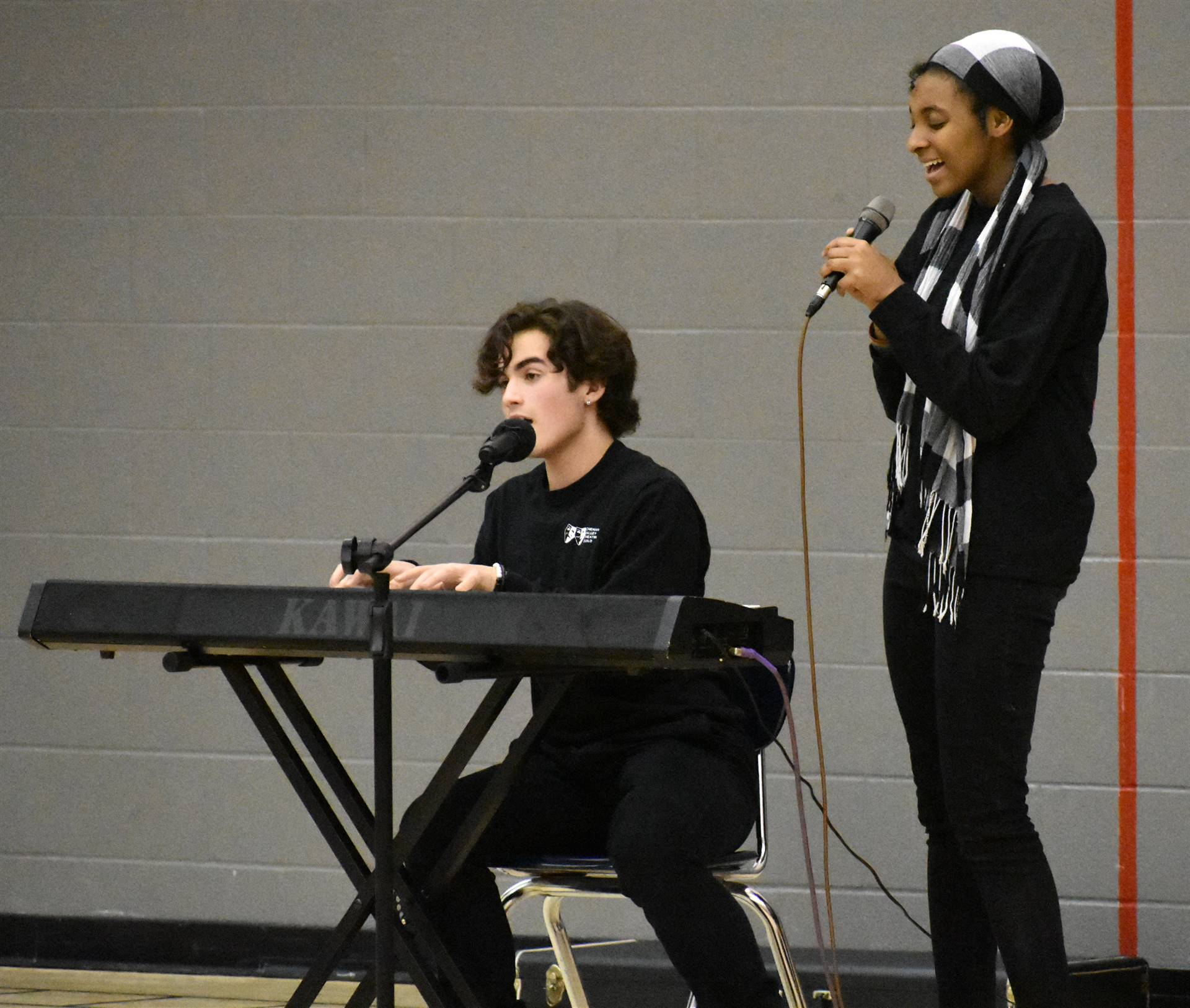 person singing and person playing piano and singing at big gifted give event