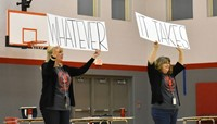teachers holding up signs that read whatever it takes