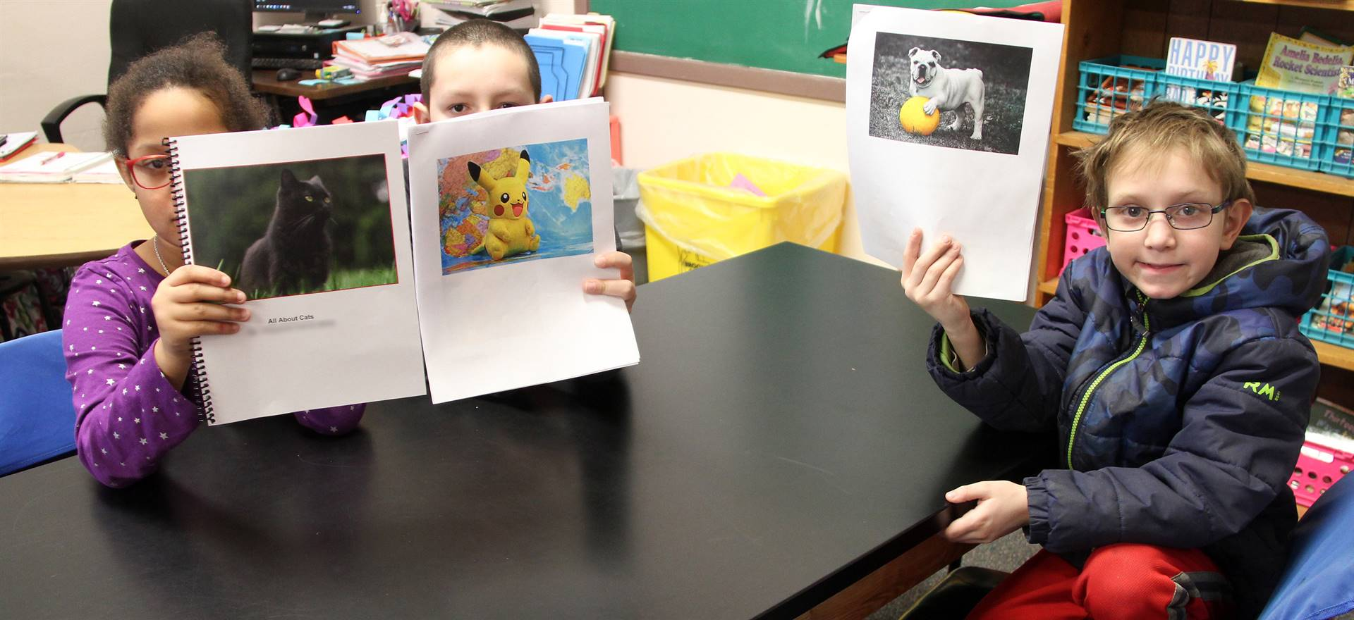 three students holding up stories