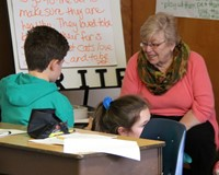 students reading to adult