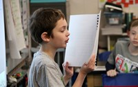 student reading story to classroom