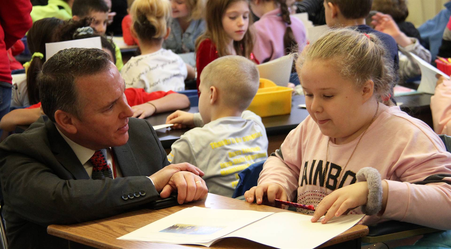 student reading to superintendent