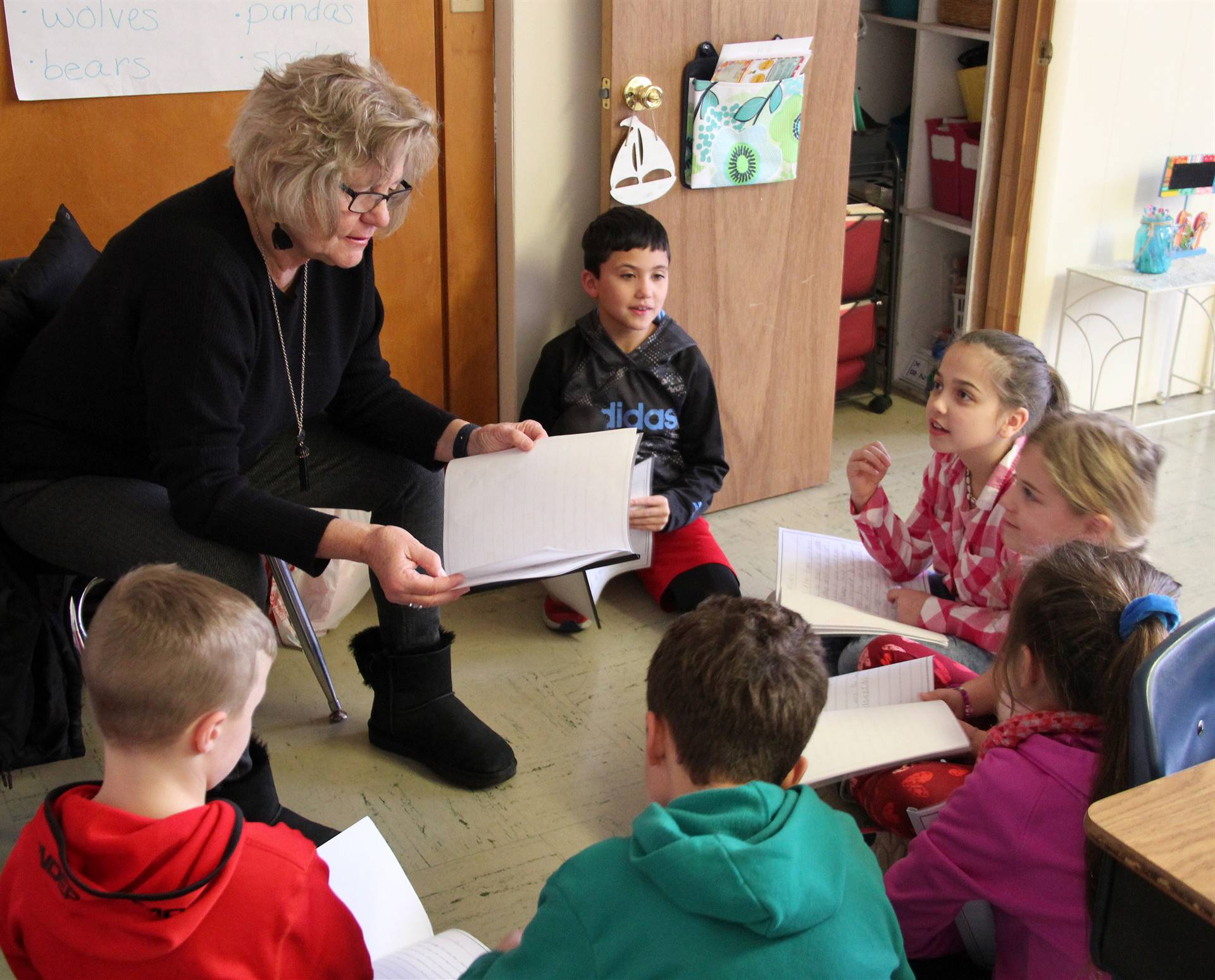 students reading with adult