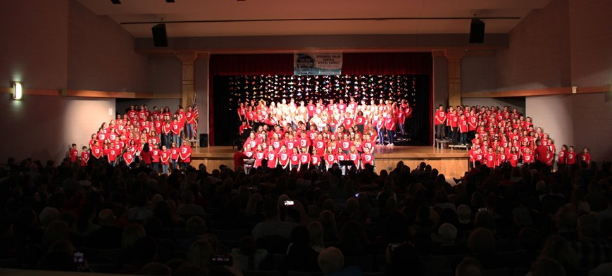 students singing in auditorium