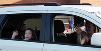 student waving in car