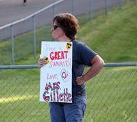 teacher holding sign