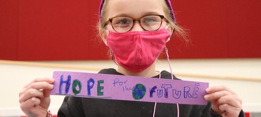 STUDENT HOLDING SIGN THAT SAYS HOPE FOR THE FUTURE